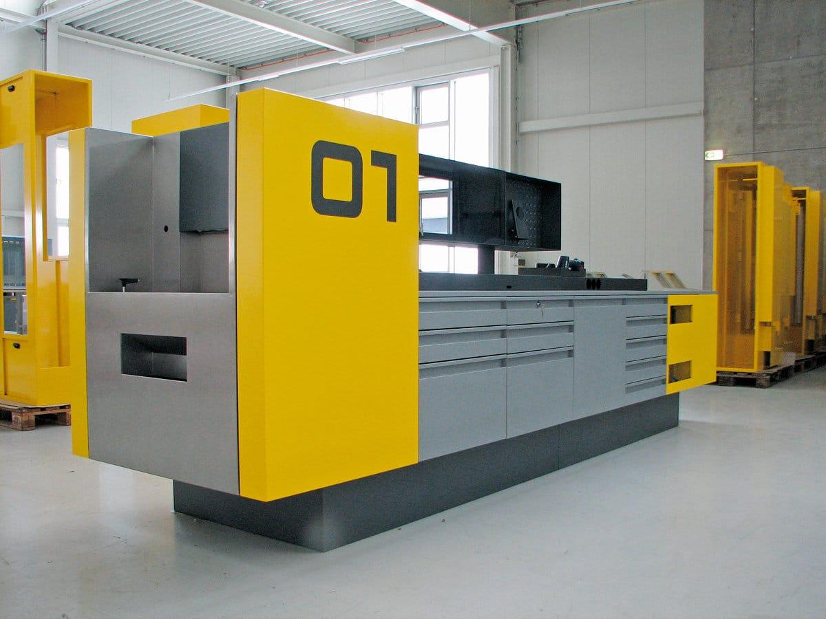 KFZ-Werkstatt Arbeitsstationen - KFZ-Werkstatt Arbeitsstationen  mit einem stirnseitig integrierten Nassbereich und einem Lagersystem für Ersatzteile und Werkzeuge.