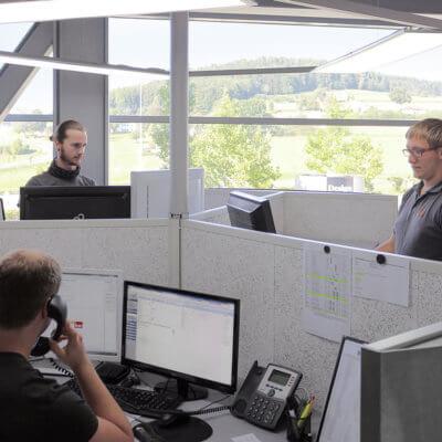 FastForward Tisch bei Schinko - Mitarbeiter stehen und sitzen am FastForward Tisch im Betriebsgebäude bei Schinko